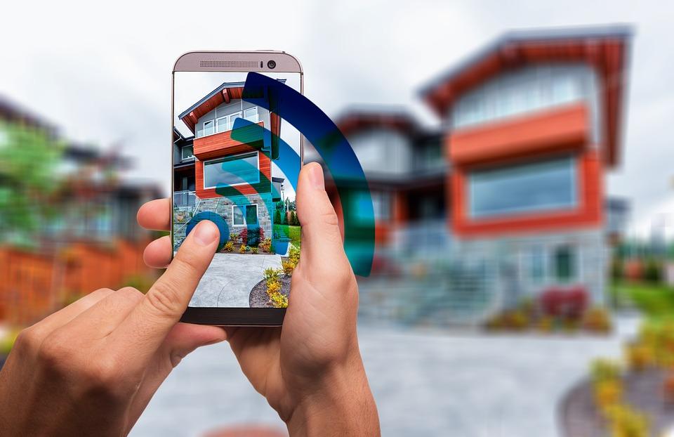 Smartphone auf dem App geöffnet ist, großes Wlan-Symbol im Vordergrund, im Hintergrund ein Haus