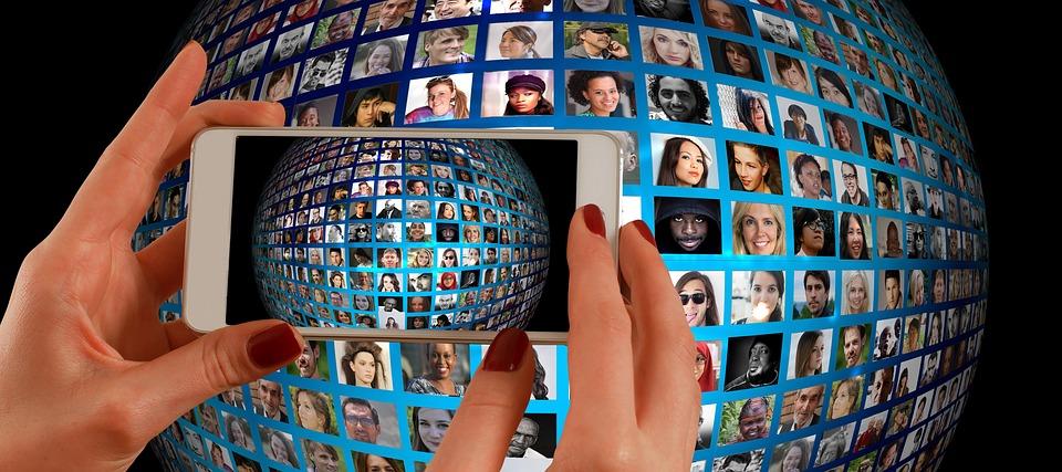 Smartphone quer in Händen gehalten, zeigt auf eine Wand mit vielen Fotos von Köpfen